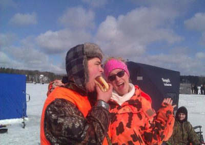 Man eating hotdog and lady laughing