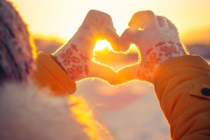 Woman hands in winter gloves Heart symbol