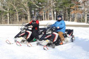 People riding snowmobiles
