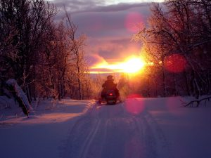 Snowmobile on trail at sunset
