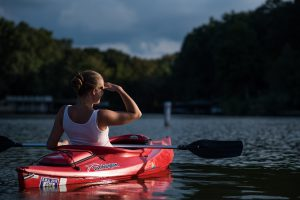 Woman in kayak looking over water