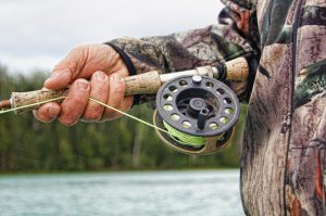 Close up on man holding fishing reel
