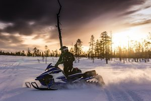 Person snowmobiling at sunset