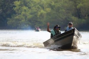 Men waving from boat on river