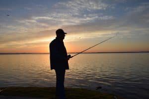 Silhouette of man fishing at sunset