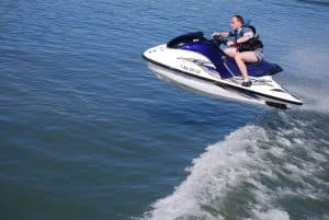 Man jumping jet ski on lake