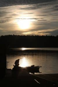 Silhouette of man in boat on lake at sunset