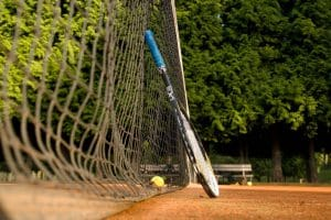 Tennis racket propped on tennis court
