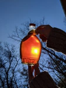 Maple syrup bottle held up to sunlight
