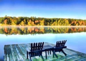 Adirondack chairs on dock over fall lake view