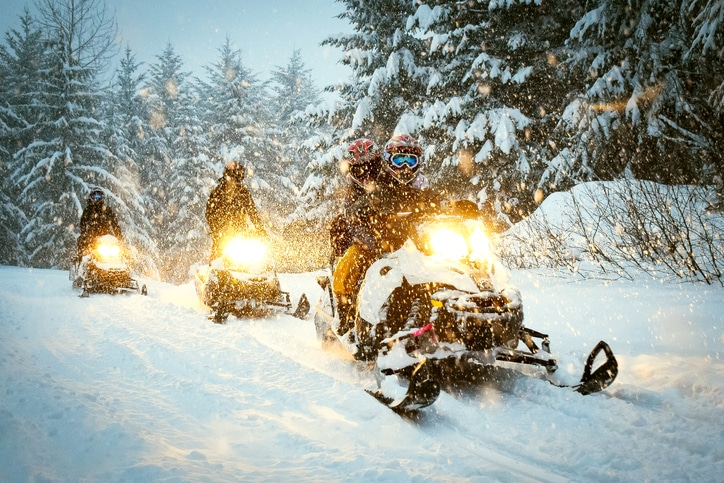Couple snow mobile in snow storm